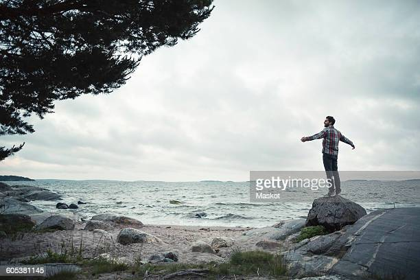Rear view of wonderlust man standing with arms outstretched on rock by sea