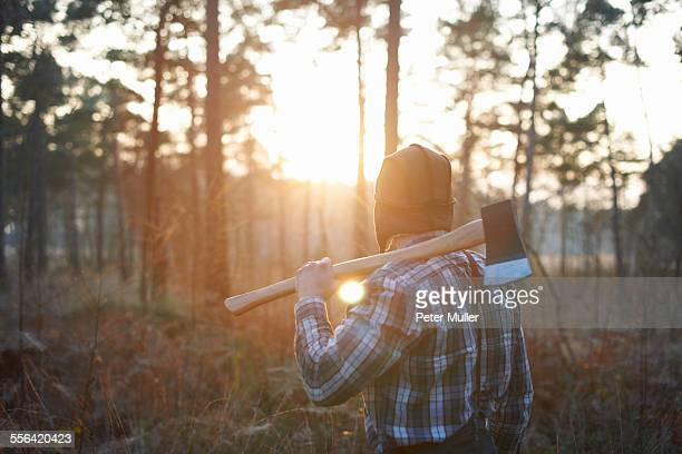 Rear view of woodsman with axe over his shoulder in forest at sunset