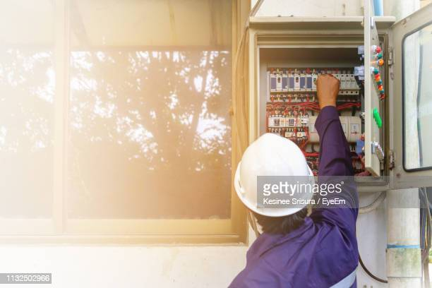 rear view of worker examining electric box - electrical box stock pictures, royalty-free photos & images