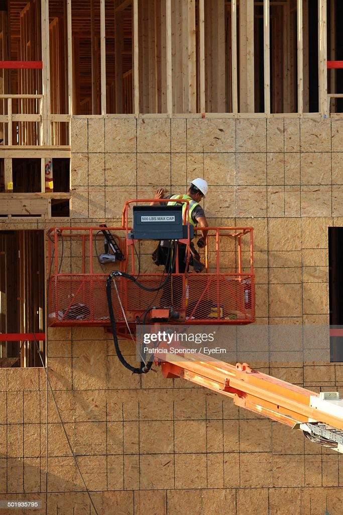 Rear View Of Worker On Towable Manlift At Construction Site