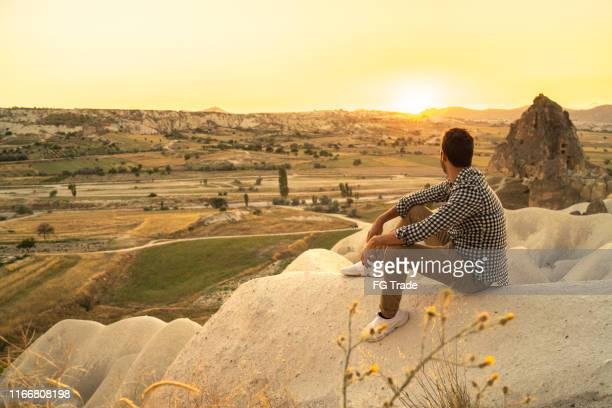 rear view of young adult man sitting and looking at valley - pardo brazilian stock pictures, royalty-free photos & images