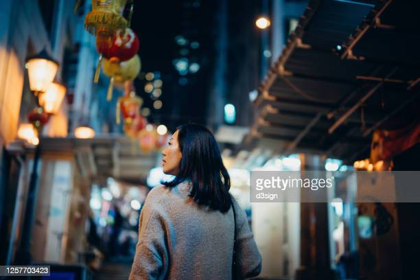 rear view of young asian female traveller exploring and strolling in city street at night, with traditional chinese red lanterns hanging in the background - chinese culture stock pictures, royalty-free photos & images