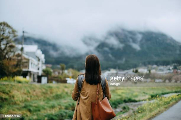 rear view of young asian mother carrying little toddler girl walking outdoors and looking far away towards the beautiful nature scene - 郊外の風景 ストックフォトと画像