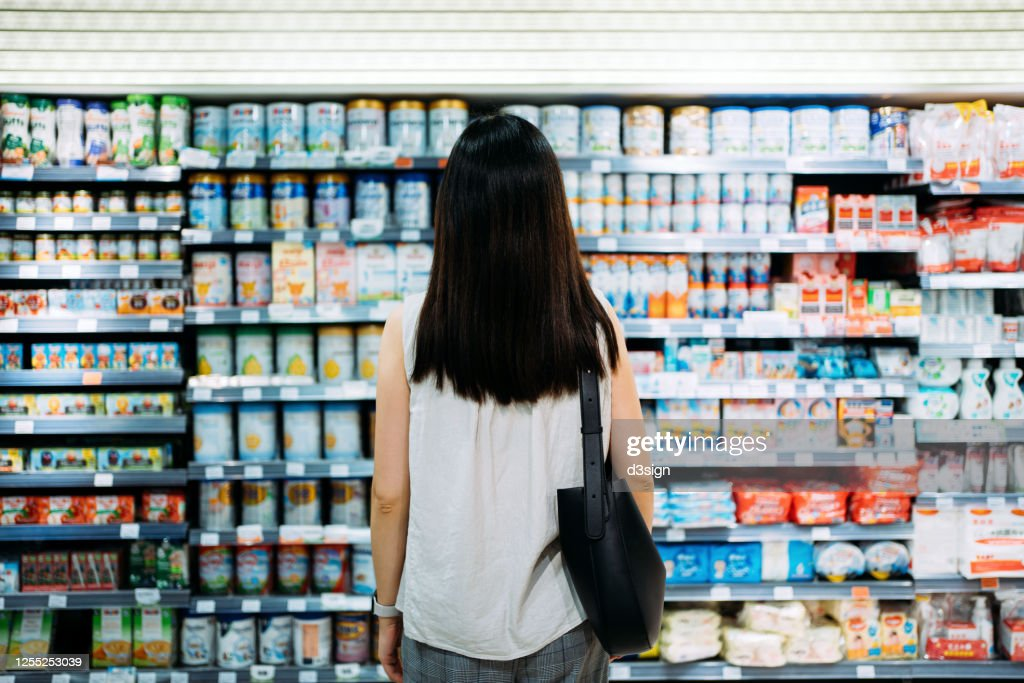 Rear view of young Asian mother groceries shopping for baby products in a supermarket. She is standing in front of the baby product aisle and have no idea which product to choose from : Stock Photo