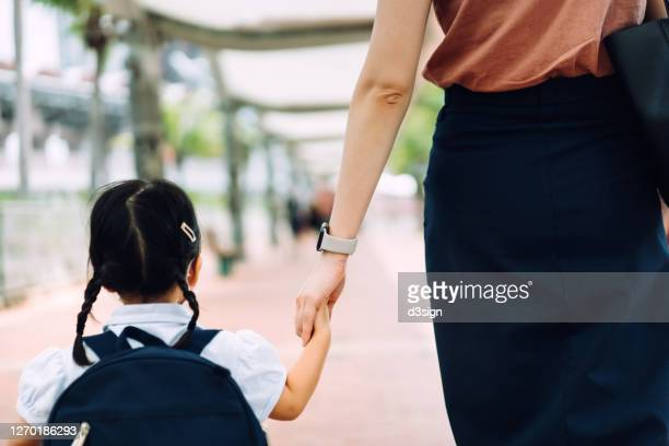 rear view of young asian mother taking her little daughter to school, they are holding hands and walking in the city street in the morning - education stock pictures, royalty-free photos & images