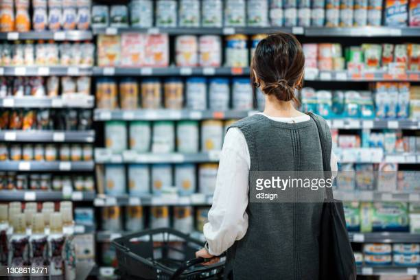 rear view of young asian mother with a shopping cart grocery shopping for baby products in a supermarket. she is standing in front of the baby product aisle and have no idea which product to choose from - food and drink stock pictures, royalty-free photos & images