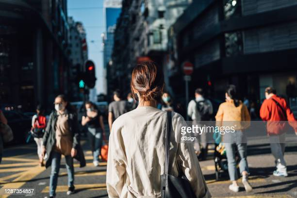 rear view of young asian woman commuting to work in city in the fresh morning, crossing street amidst crowd of pedestrians. daily life and routine of a businesswoman - image stock pictures, royalty-free photos & images