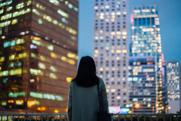 Rear view of young Asian woman standing against illuminated cityscape of Hong Kong metropolitan at night