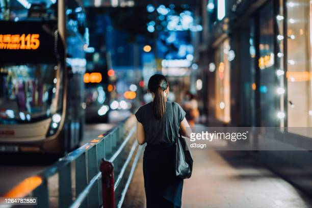 rear view of young asian woman walking on busy downtown city street after work at night, with busy traffic and illuminated city scene in background - loneliness stock pictures, royalty-free photos & images