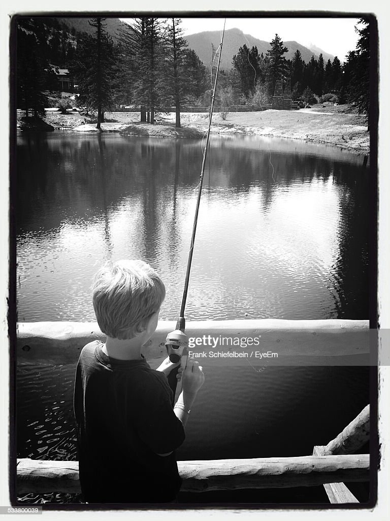 Rear View Of Young Boy Fishing From Bridge : Foto stock