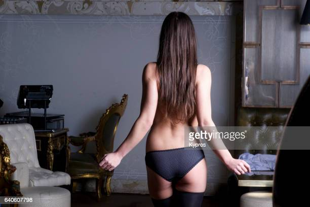 rear view of young brunette woman's back, wearing underwear, semi nude, arms - fesses culotte photos et images de collection