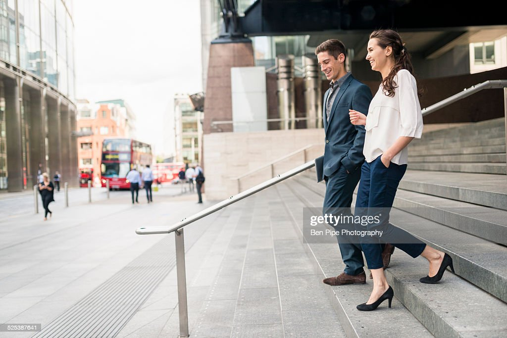 Rear view of young businessman and woman chatting whilst walking down stairway, London, UK : Stock Photo