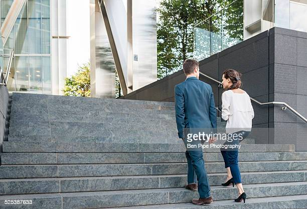 Rear view of young businessman and woman walking up stairway, London, UK