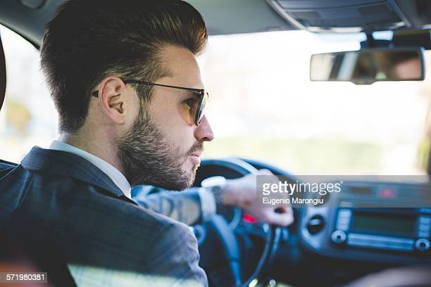 Rear view of young businessman driving car