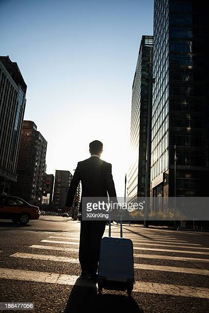Rear view of young Businessman walking down the street with luggage