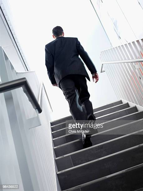 rear view of young businessman walking up stairs - ビジネスウェア ストックフォトと画像