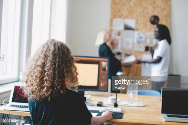 Rear view of young businesswoman using computer at table with colleagues in background at creative office