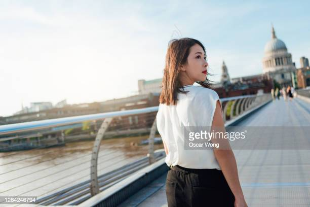 rear view of young businesswoman walking on footbridge in the city - three quarter length stock pictures, royalty-free photos & images