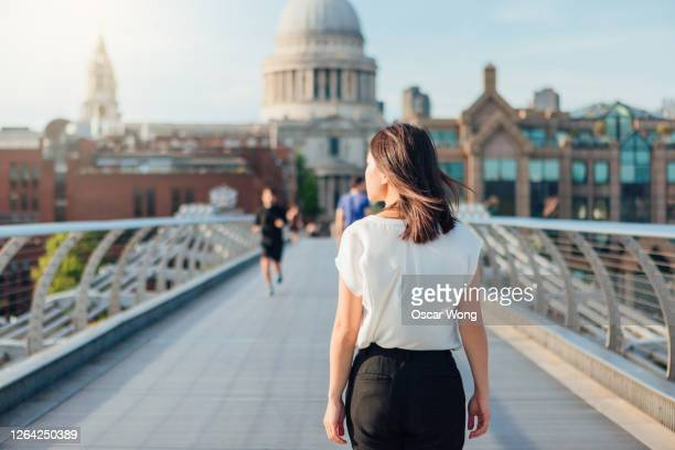 rear view of young businesswoman walking on footbridge in the city - back stock pictures, royalty-free photos & images