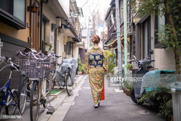 rear view of young caucasian woman in kimono walking in narrow alley - obi sash stock pictures, royalty-free photos & images