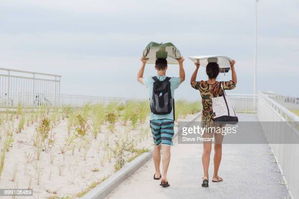 'Rear view of young couple carrying surfboards on heads, Rockaway Beach, New York State, USA'