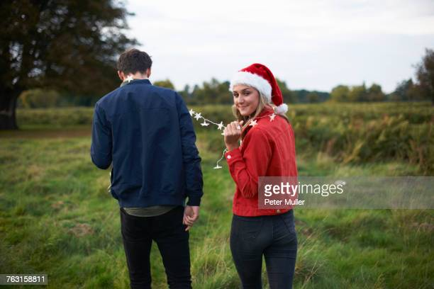 rear view of young couple in santa hat and xmas light garland strolling in field - country christmas stockfoto's en -beelden