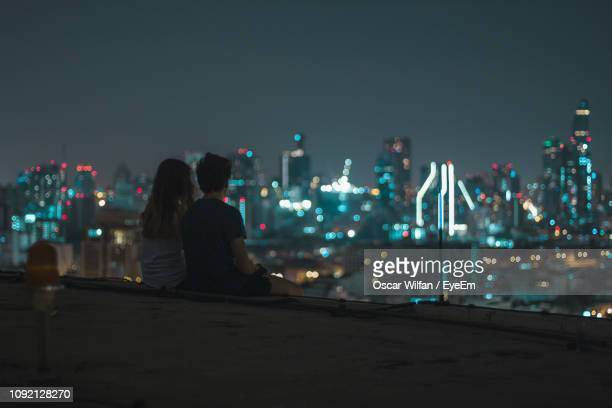 rear view of young couple looking at cityscape while sitting on building terrace against sky - dach stock-fotos und bilder