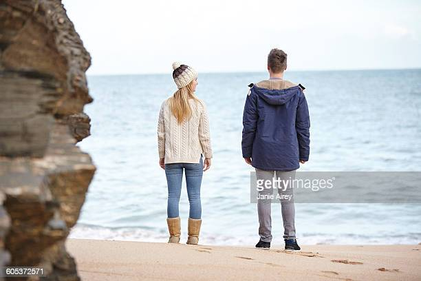 Rear view of young couple looking out from beach, Constantine Bay, Cornwall, UK