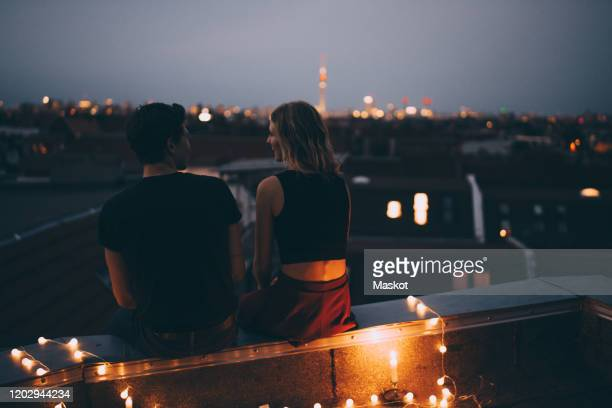 rear view of young couple sitting on illuminated terrace in city at dusk - love stock pictures, royalty-free photos & images
