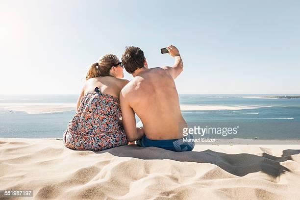 Rear view of young couple taking selfie, Dune de Pilat, France