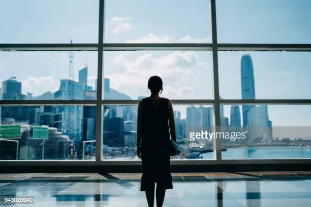 Rear view of young executive looking through window to the prosperous city skyline of Hong Kong
