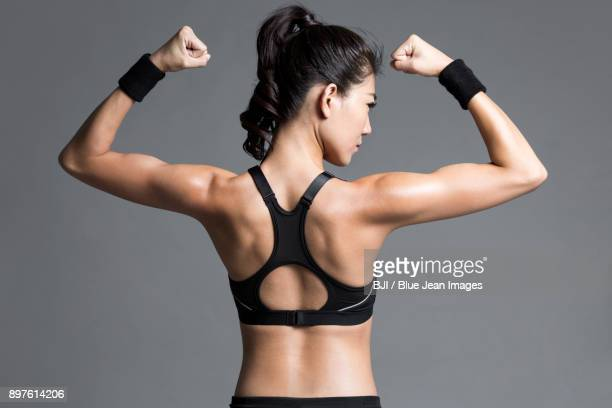 rear view of young female athlete flexing muscles - asian female bodybuilder stock photos and pictures