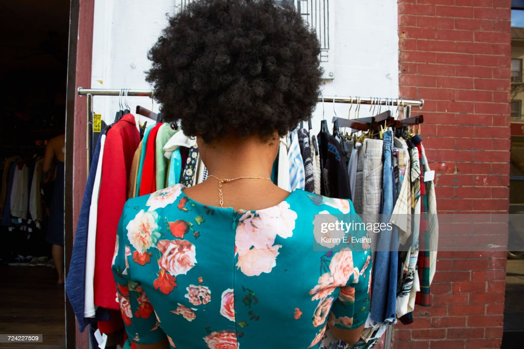 Rear view of young female fashion blogger with afro hair looking at vintage clothes rail, New York, USA : Stock-Foto