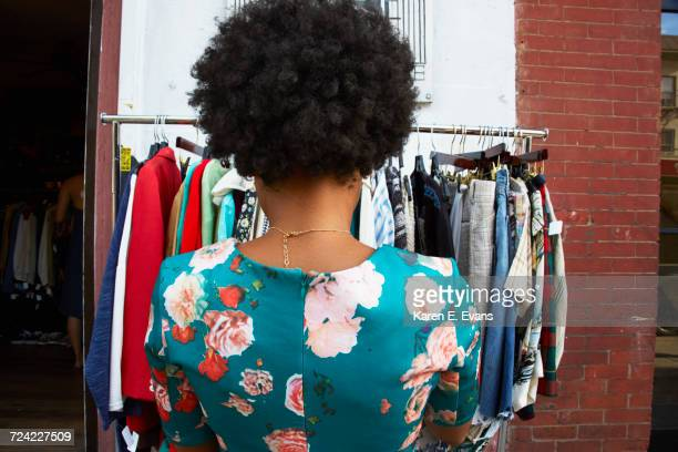 Rear view of young female fashion blogger with afro hair looking at vintage clothes rail, New York, USA