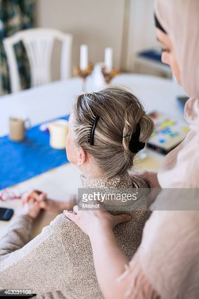 Rear view of young female home caregiver giving shoulder massage to grandmother at home