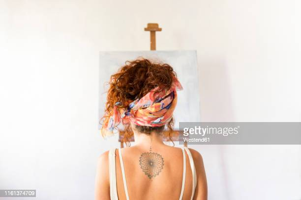rear view of young female painter in art studio in front of empty canvas - backless stock pictures, royalty-free photos & images