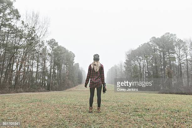 rear view of young female photographer standing in misty field - cary stockfoto's en -beelden