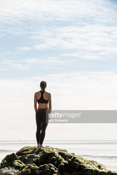 Rear view of young female runner looking out at sea from beach rock