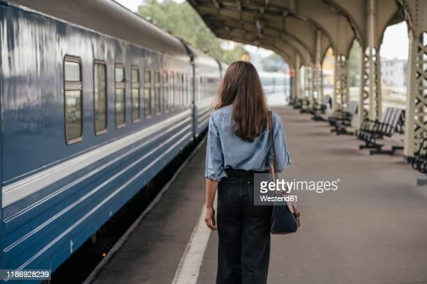 rear view of young female traveller walking on the platform - rückansicht stock-fotos und bilder