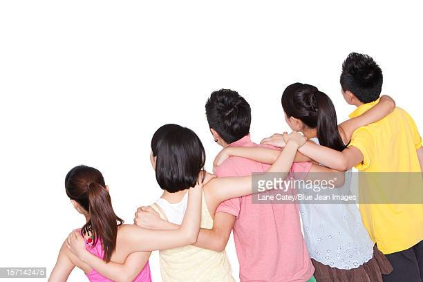 Rear view of young friends putting arms around each other