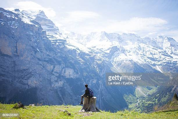 rear view of young hiker sitting on tree stump in front of snowcapped mountains - my lai sit fotografías e imágenes de stock