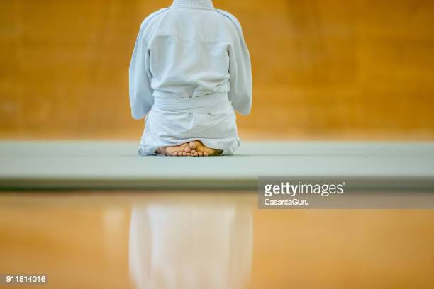 rear view of young judoist kneeling - submission combat sport stock pictures, royalty-free photos & images