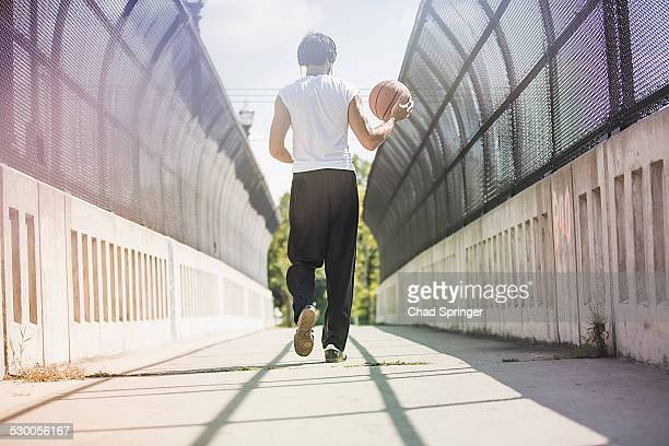 Rear view of young male basketball player walking along footbridge carrying ball
