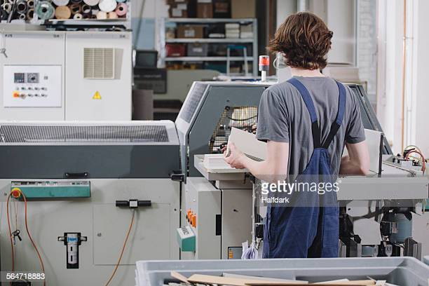Rear view of young male worker operating machine in factory