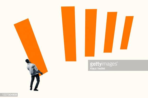 rear view of young man arranging orange bar graph - racism stock pictures, royalty-free photos & images