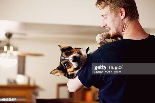 rear view of young man carrying dog while standing at home - carrying stock pictures, royalty-free photos & images