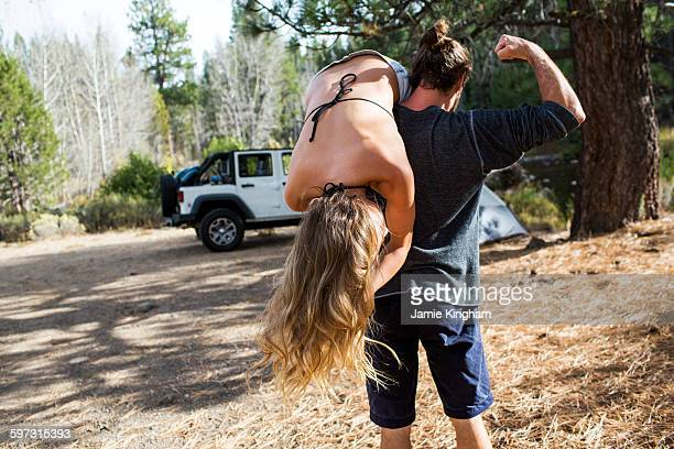 Rear view of young man carrying girlfriend over shoulder at forest campsite, Lake Tahoe, Nevada, USA