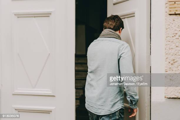 rear view of young man entering house - entrata foto e immagini stock