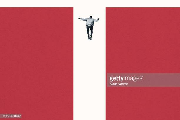 rear view of young man falling between red columns - graphic accident photos stock pictures, royalty-free photos & images