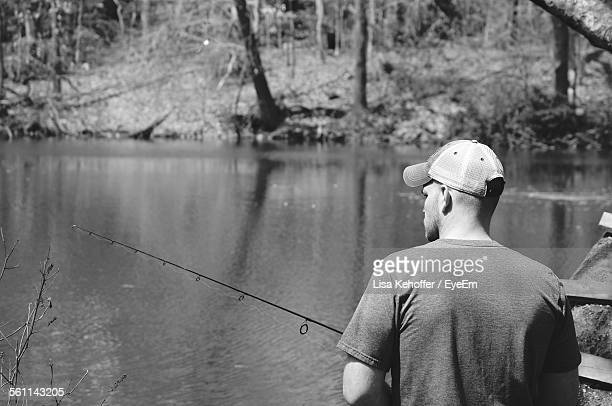 Rear View Of Young Man Fishing In Lake